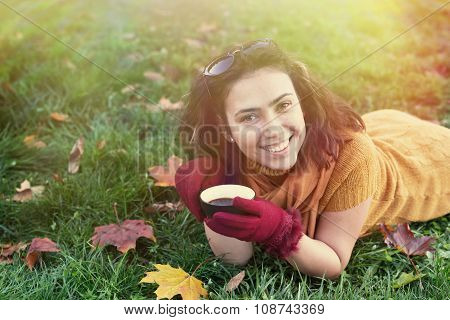 Smiling Woman Lying On Autumn Leaves