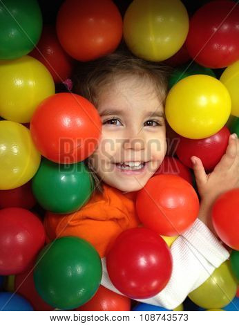 Authentic image of a toddler girl laughing in a ball pit