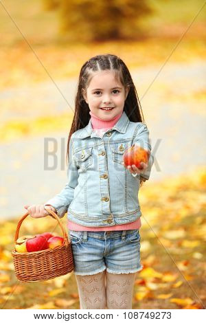 Beautiful little girl holding basket of apples, outdoor