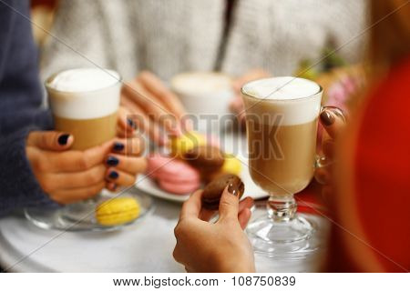 Women meeting in cafe and drinking latte