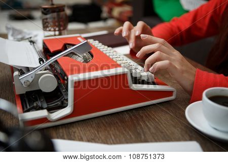 woman at table typing on typewriter