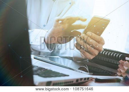 Businessman Hand Using Laptop And Mobile Phone On Wooden Desk As Concept