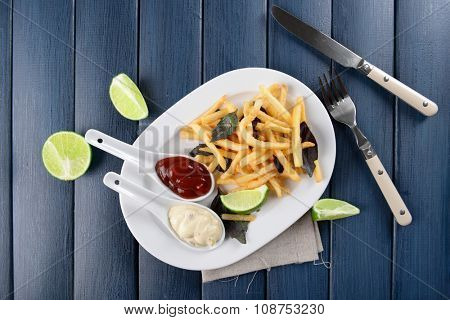 French fried potatoes with sauce and lime on white tray