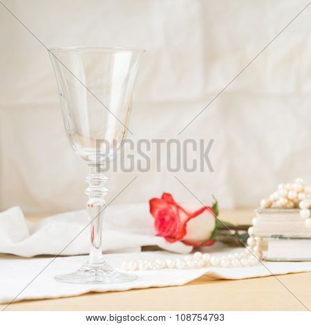 Beautiful Empty Glass With Vintage Books And Pearls