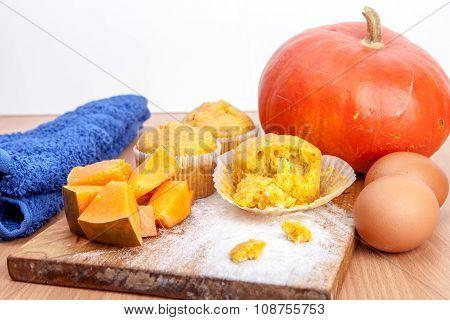 Three Cupcakes, Pumpkin And Baking Kitchenware On Kitchen