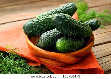 Fresh cucumbers with red cotton serviette on wooden table