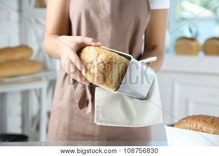 Baker with freshly baked bread in kitchen of bakery