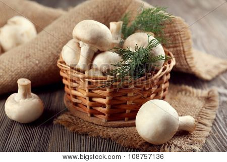 Champignon mushrooms, a basket, dill and sacking mat on wooden background