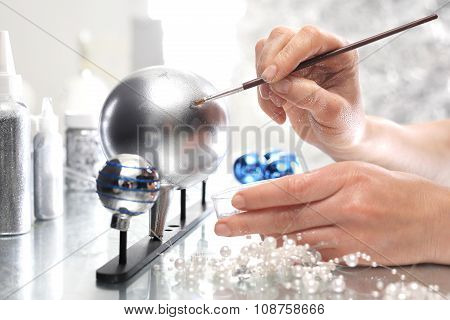 Work on decorating Christmas baubles. A woman painting a design on a silver bauble