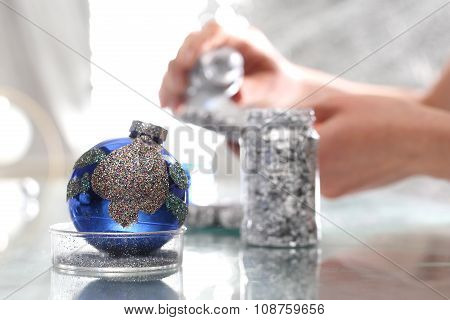 Glitter bauble. A woman showering Christmas bauble silver glitter.