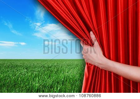 Human hand opens red curtain on field background