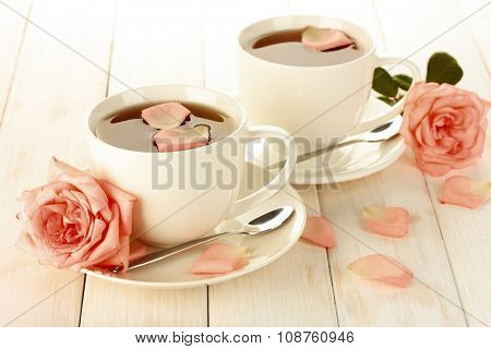 Two cups of tea with creamy roses on white wooden table