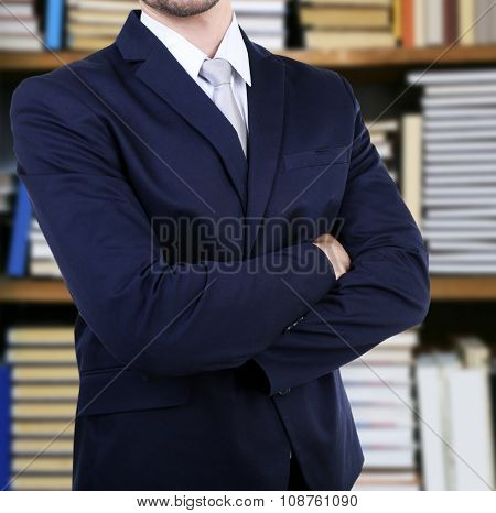 Man in suit on blurred bookshelves background