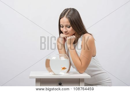 The Girl Sits Near The Aquarium With Goldfish And Looks At It