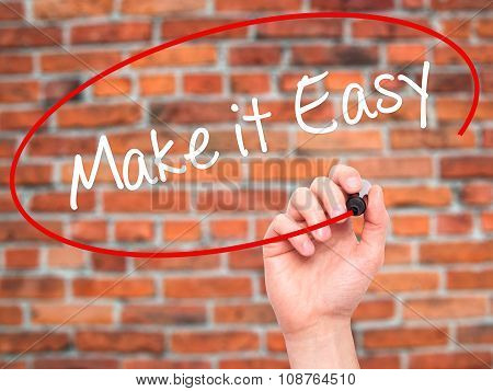 Man Hand writing Make it Easy with black marker on visual screen.