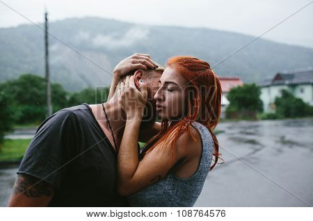 beautiful couple hugging in the rain