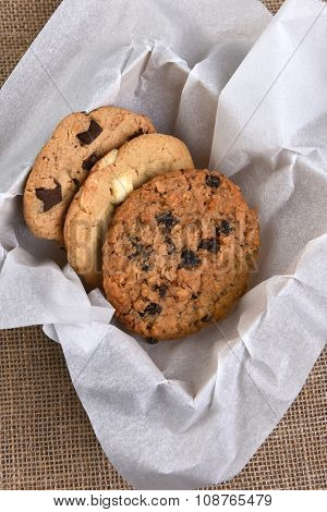 High angle view of a box of assorted gourmet cookies. Chocolate, oatmeal raisin and white chocolate chip cookies closeup in a box stuffed with paper on a burlap surface.