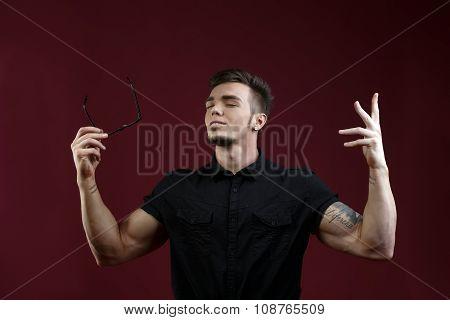 Studio image of stylish guy took off his glasses