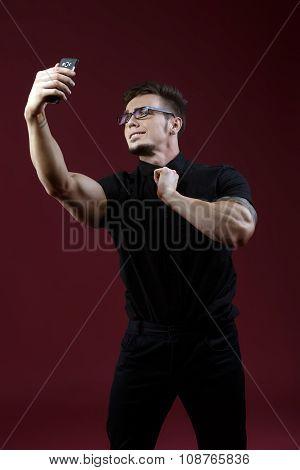 Stylish young guy doing selfie in studio