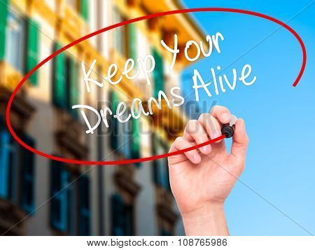 Man Hand writing Keep Your Dreams Alive with black marker on visual screen.