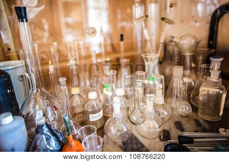 Glass Bottles, Test Tubes, Flasks And Cups In An Old Chemical Laboratory