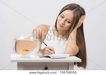 Girl Writing In A Notebook Desire To Fulfill A Goldfish