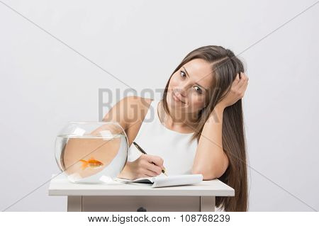 Girl Writing In A Notebook, Standing Next To An Aquarium With Goldfish
