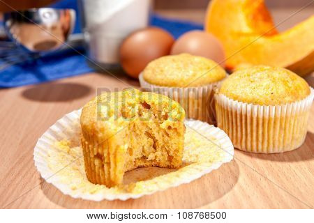 Bite-off Cupcake, Pumpkin And Baking Kitchenware On Table