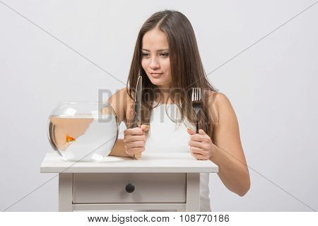 Girl Holding Knife And Fork In Hand And With An Appetite For Looking At The Little Goldfish
