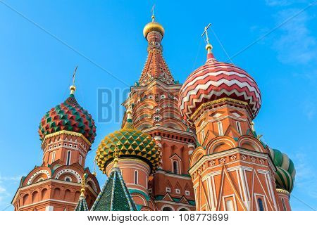 Domes of St. Basil's cathedral on Red Square of Moscow against blue sky and white clouds