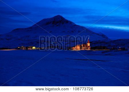 Icelandic winter landscape with church on the background of the mountains at dusk. near Akureyri, Iceland
