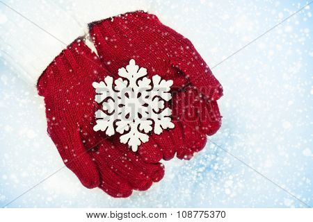 Female hands in mittens with sparkling snowflake on white snow background