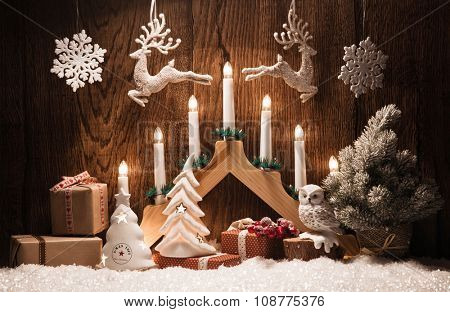 Christmas decoration with gifts and candles on wooden background