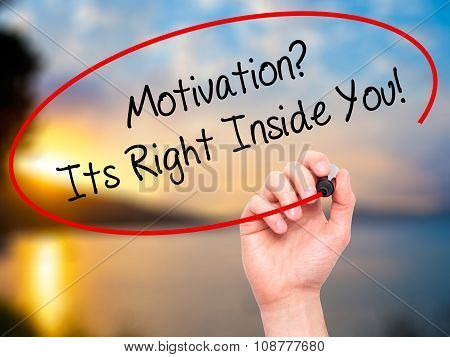 Man Hand writing Motivation? Its Right Inside You! with black marker on visual screen.