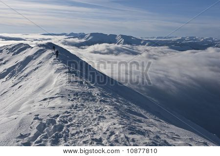 Two Climbers On A Mountain Top In Winter