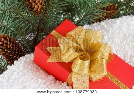 Gift Box With Ribbon In Snow  Under Pine Tree