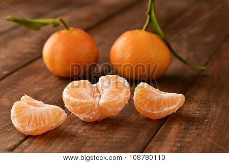 closeup of a pile of mandarin oranges, one of them peeled, on a rustic wooden surface