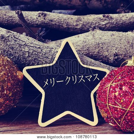 a star-shaped chalkboard with the text merry christmas written in japanese surrounded by christmas balls and logs