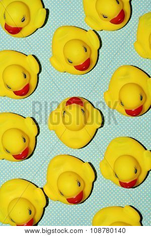 a pile of rubber ducks, one of them countercurrent, on a dot-patterned background, with a hard-shadow processing