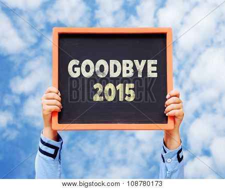 Hands Holding Blackboard With Goodbye 2015 Year.
