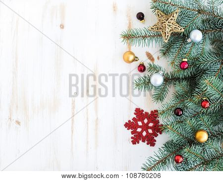 Christmas or New Year decoration background: fur-tree branches, colorful glass balls and glittering