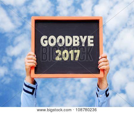 Hands Holding Blackboard With Goodbye 2017 Year.