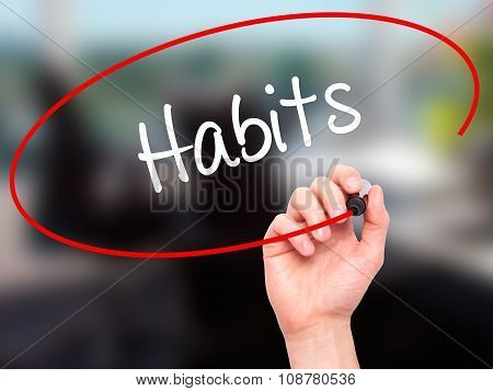 Man Hand writing Habits with black marker on visual screen.