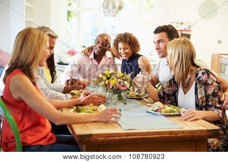 Mature Friends Sitting Around Table At Dinner Party