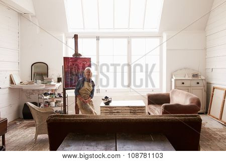 Female Artist Working On Painting In Bright Daylight Studio