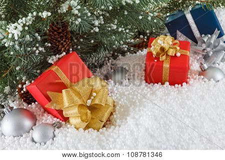 Red And Blue Boxes With Gold Ribbon In Snow  Under Pine Tree