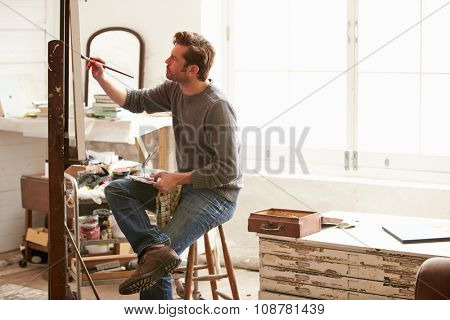 Male Artist Working On Painting In Studio