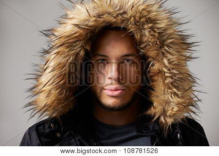 Studio Portrait Of Young Man Wearing Winter Coat