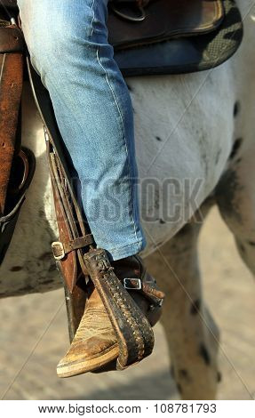 Cowboy Foot In The Stirrup Of The Horse During The Ride