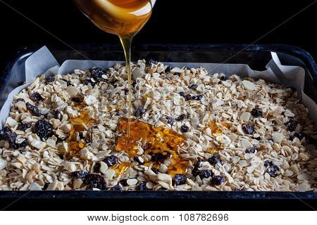 Granola in a baking tray with honey from side